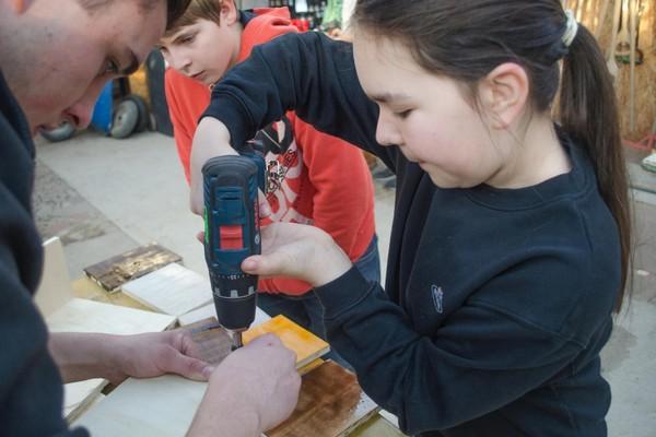 Minigärtner Nürtingen und Auszubildende vom Betrieb Bühler Baum und Garten arbeiten zusammen am Vogelhaus